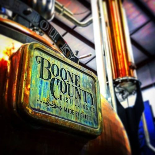 Green and copper sign reading Boone County Distilling Co. Made by Ghosts.