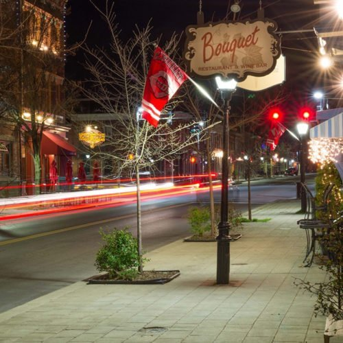 Main street in Mainstrasse Village in Covington KY at night, with glowing red and white lights and the sign for Bouquet Restaurant & Wine Bar hanging above