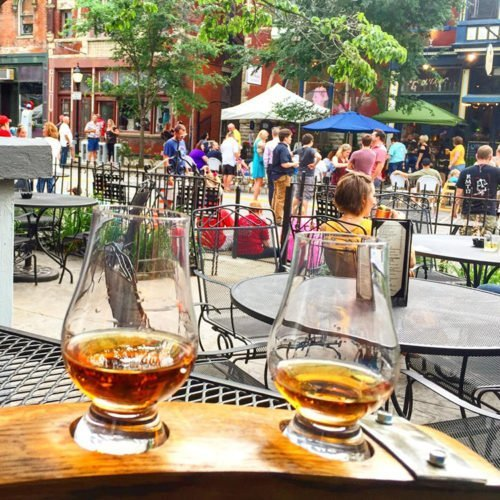 A bourbon flight up close on the pation at Bourbon Haus bourbon bar in Mainstrasse Village. Lots of people on the street in the background in front of Bouquet Restaurant.