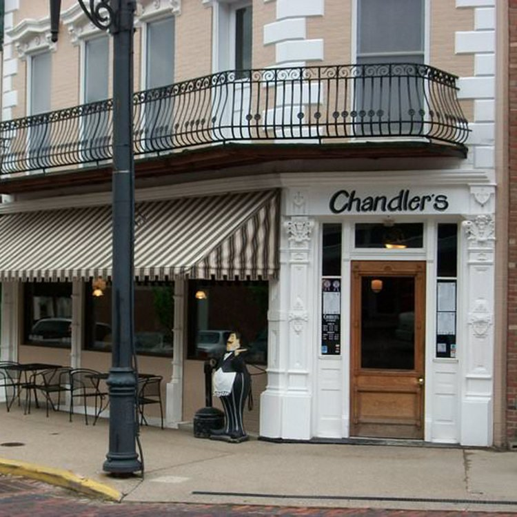 """A white stone and beige brick storefront with black iron railing on the second story and the name """"Chandler's"""" over the white trimmed door."""