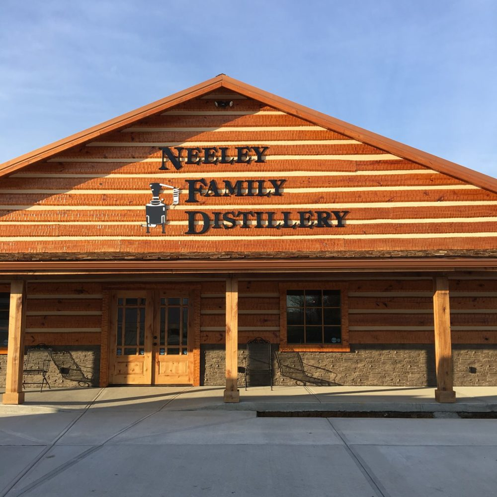 Neeley Family Distillery's entrance with the name written on the wood roof and wood doors leading inside