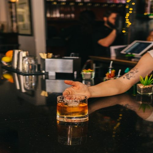 tumbler of bourbon on wood bar with woman's hand offering it in the background