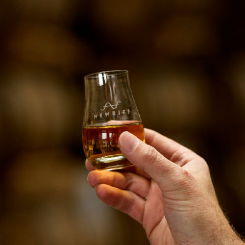 man's hand holding a glen cairn glass with new riff bourbon inside