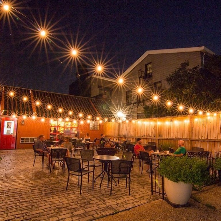 strings of white lights shining in the night over the brick patio filled with black chairs at prohibition bourbon bar