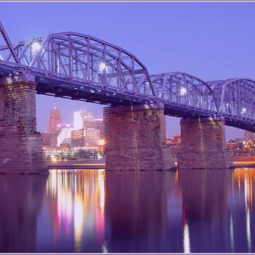 A purple colored steel bridge crossing the ohio river on stone supports between newport kentucky and cincinnati ohio