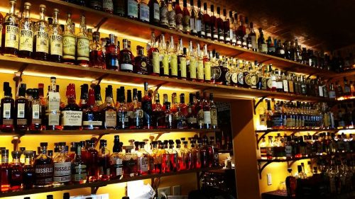 a yellow wall with the world's largest collection of bourbon arranged in front of it at Prohibition Bourbon Bar