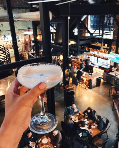 a cocktail being held up over a view of Wiseguy Lounge in Mainstrasse in Covington, Kentucky
