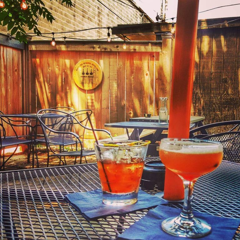 two bourbon cocktails on a metal table with the OKBB sign hanging on wood wall behind them