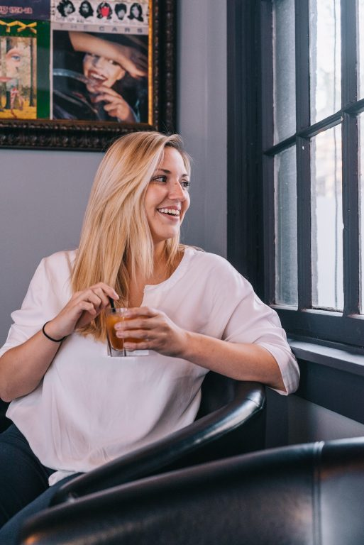 blonde woman enjoying a bourbon drink at bourbon haus 1841 in covington ky mainstrasse village