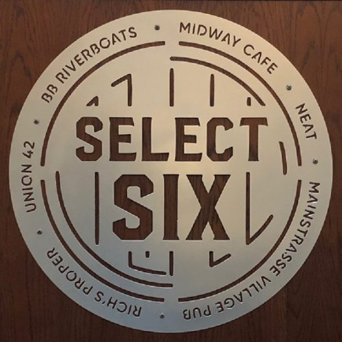 A round sign with the names of the Northern Kentucky Select Six venues printed around the circumference: BB Riverboats, Midway Cafe, Neat, Mainstrasse Village Pub, Rich's Proper, Union 42.