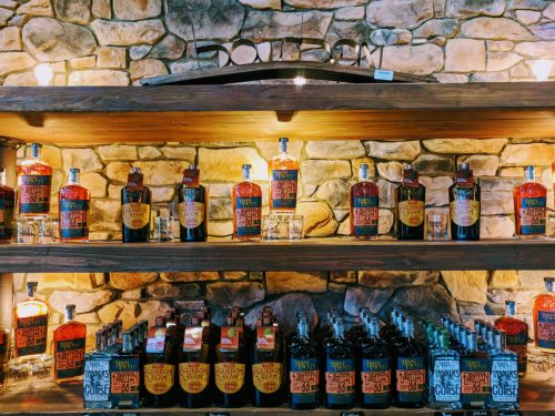 Rows of Boone County Distilling's spirits on wood shelves with a stone wall background