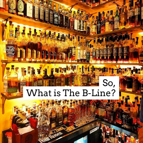 A golden yellow corner filled with shelves of hundreds of bourbons at Prohibition Bourbon Bar with the words So, What is The B-Line?