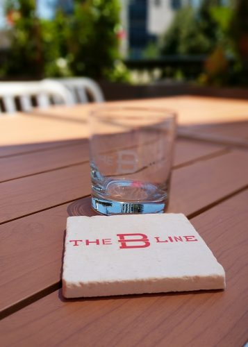 A whiskey glass engraved with The B-Line behind a white marble coaster with The B-Line written in red letters