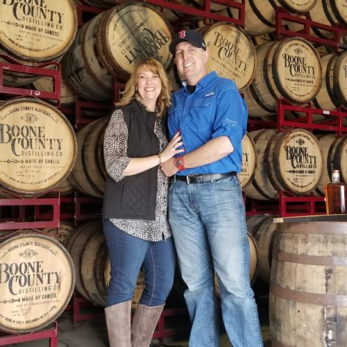 man and woman posing and smiling in front of bourbon barrels at boone county distilling in northern kentucky