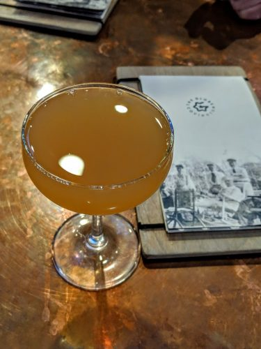 A golden bourbon cocktail called Pass the Buck next to the menu at The Globe bourbon bar in Covington, KY