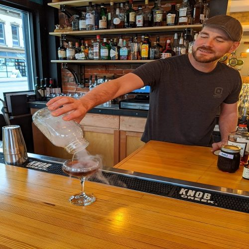 Bill Whitlow, Owner of Rich's Proper, pouring a smoke cocktail