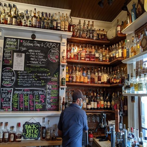 The famous chalkboard bourbon menu at Old Kentucky Bourbon Bar with Bartender standing in front of wall of bourbon bottles