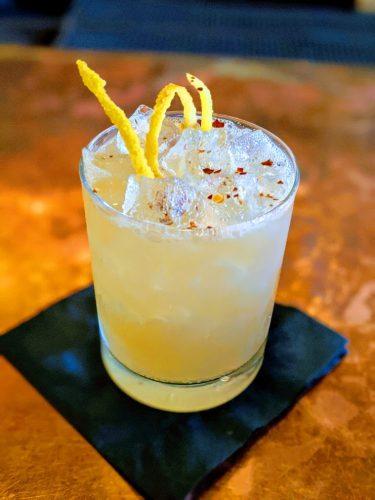 A closeup of lemon colored jalapeno cocktail at okbb