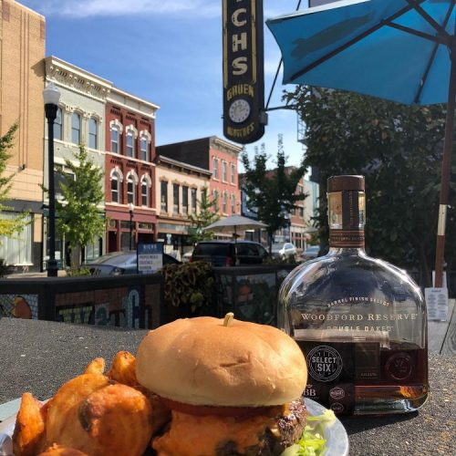 Close up of a burger and bottle of Woodford Reserve bourbon on a patio table in the sunshine at Rich's Proper Food and Drink in Covington Kentucky