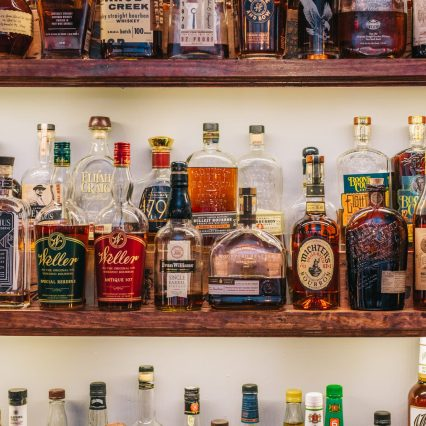 photo of numerous bourbon bottles on display on a shelf at the bar of bourbon haus 1841 in covington ky mainstrasse village