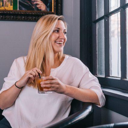 blonde woman enjoying a bourbon drink at bourbon haus 1841 in covington ky mainstrasse village