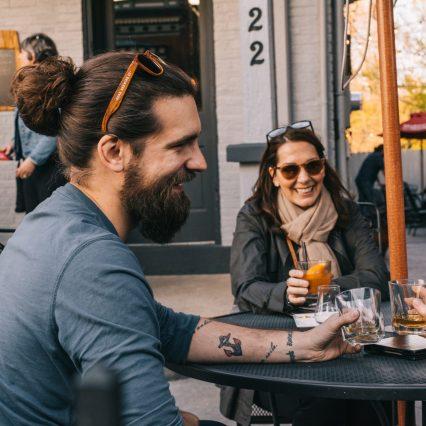 bearded man enjoying a bourbon drink on the patio of bourbon haus 1841 in covington ky mainstrasse village