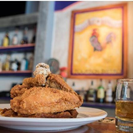 The golden and purple sign for the Purple Poulet restaurant hanging behind a plate of their famous fried chicken and a glass of Kentucky bourbon