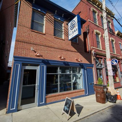 """a red brick building with blue trim and a blue and white sign reading """"The Globe"""""""
