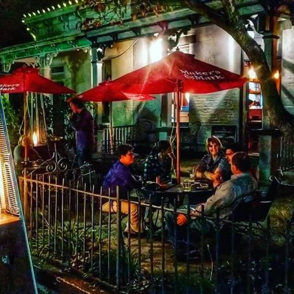 the patio at Bourbon Haus in Covington Kentucky with red umbrellas