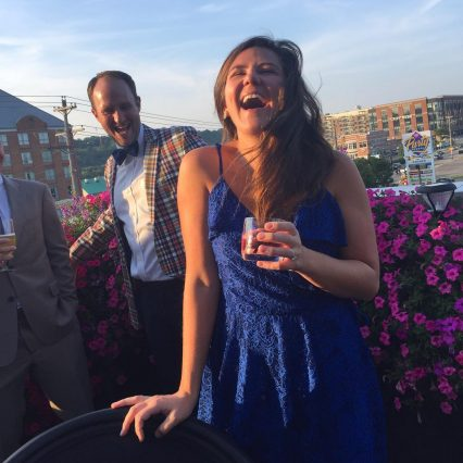 Girl in blue dress laughing while holding cocktail on patio at New Riff Distilling in Newport, Kentucky.