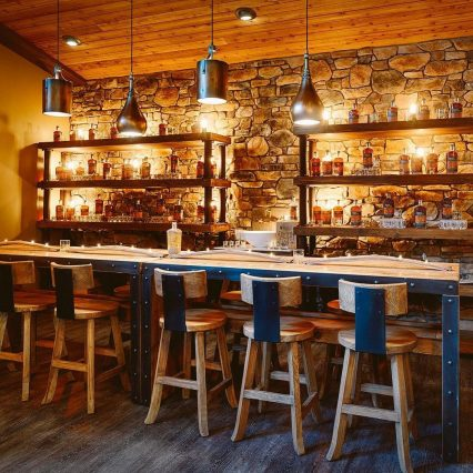 Tasting room and bar at boone county distilling company in northern kentucky. stone walls, bourbon on shelves behind the barm and bar stools in a rustic setting