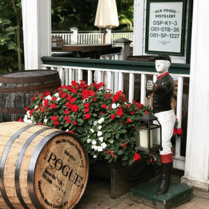 view of the grounds of Old Pogue Distillery in Maysville Kentucky. Red and white flowers with a bourbon barrel.