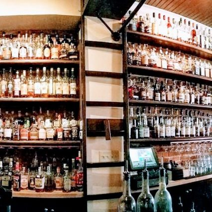 The walls at Old Kentucky Bourbon Bar, covered in built-in shelves that are full of hundreds of bottles of bourbon