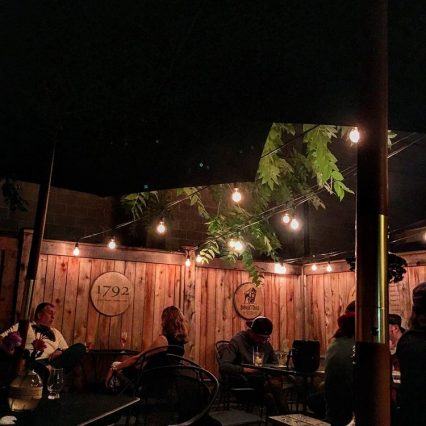 The wood privacy wall on the patio at Old Kentucky Bourbon Bar in Mainstrasse Village, hung with signs for 1792 and Buffalo Trace bourbon. People are drinking bourbon at black patio tables under a dark night sky.
