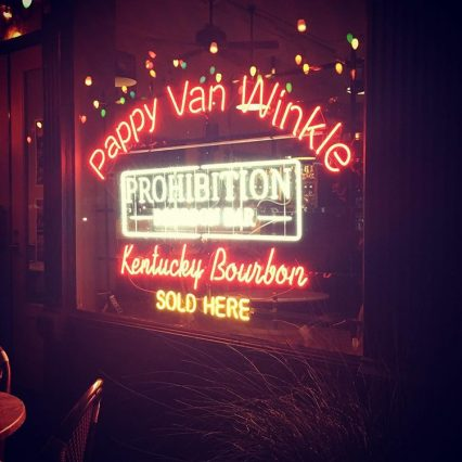 """A red and white neon sign hanging in the window of Newberry Bros. Coffee and Old Prohibition Bourbon Bar that reads """"Pappy Van Winkle Kentucky Bourbon Sold Here"""""""