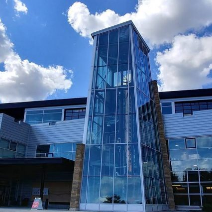 A blue sky full of white puffy clouds over the shiny blue building covered in windows of New Riff Distilling. The copper column still is visible through the glass.