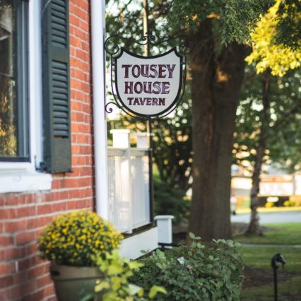 sign in front of tousey house tavern, a historic, southern restaurant with bourbon in burlington ky
