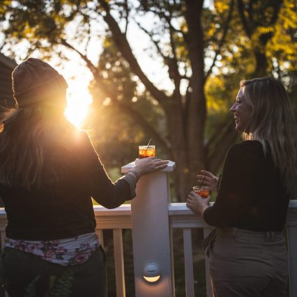 two women laughing and drinking bourbon on the patio of tousey house tavern in burlington, ky.