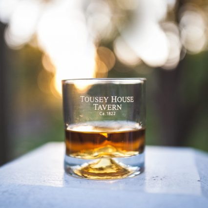close up of a bourbon glass with tousey house tavern etched in burlington ky