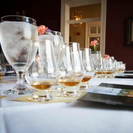 Several flights of bourbon on a white tablecloth with two water glasses, at Tousey House Tavern in Burlington, KY.